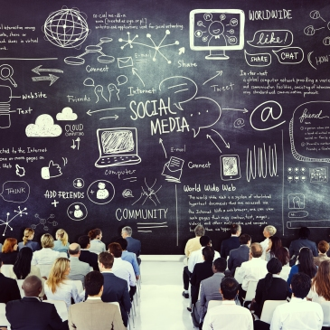 business meeting held in front of giant chalkboard with social media ideas
