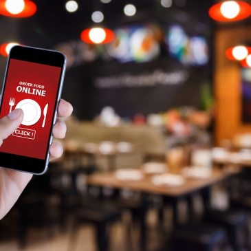 person holding phone about to place online order in a restaurant setting