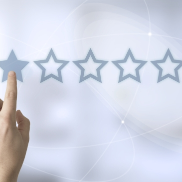 Person selecting 1 out of 5 stars on abstract background
