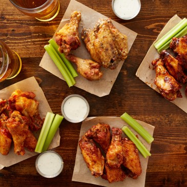 wings with dipping sauce, celery, and beer on a table