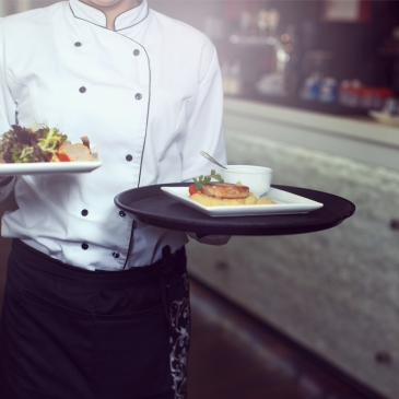 Server holding 2 plates of food