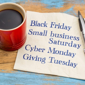 """Coffee mug next to napkin that reads """"Black Friday, Small Business Saturday, Cyber Monday, Giving Tuesday"""""""