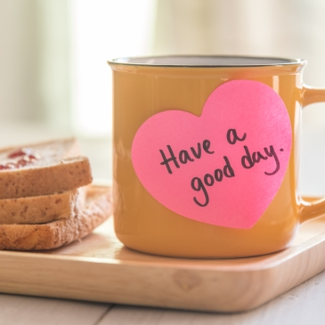 "Heart-shaped post-it note on coffee mug reading ""have a good day"""
