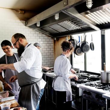 Chef and kitchen staff preparing food in restaurant kitchen